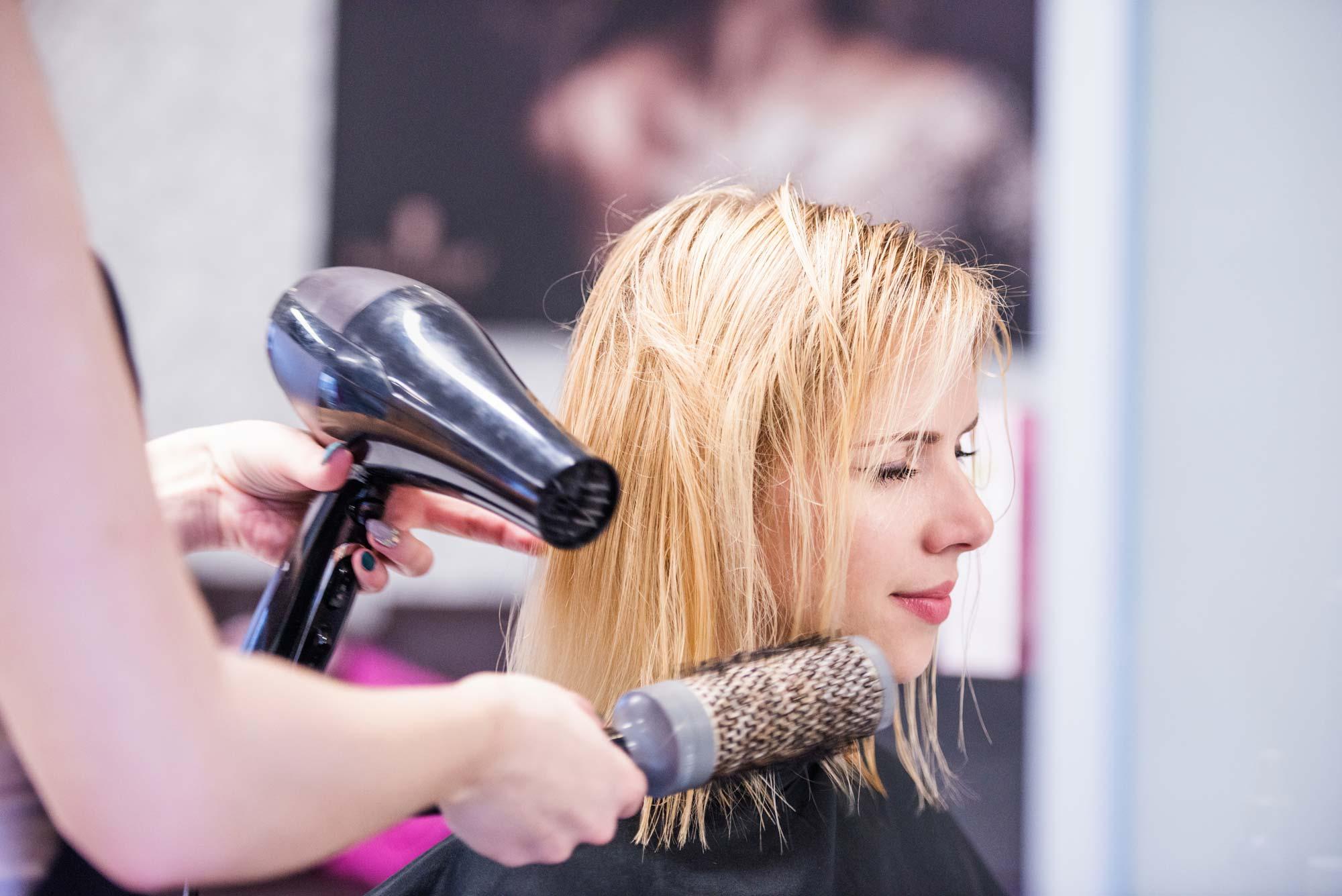 Woman cutting blond girl's hair